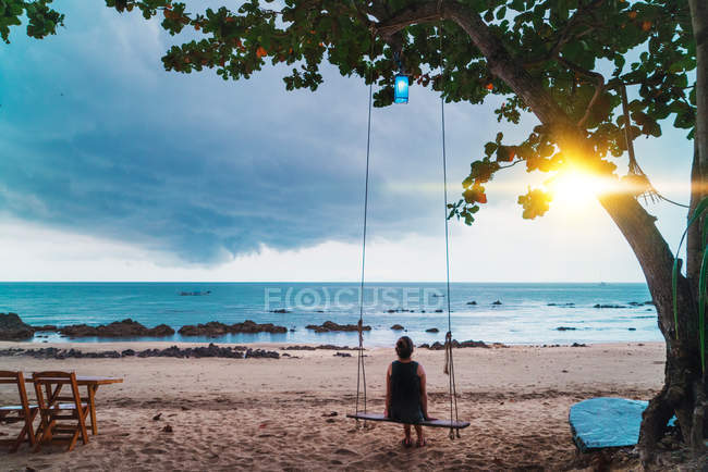 Back view of woman sitting on swings and looking at sunset at seaside. — Stock Photo