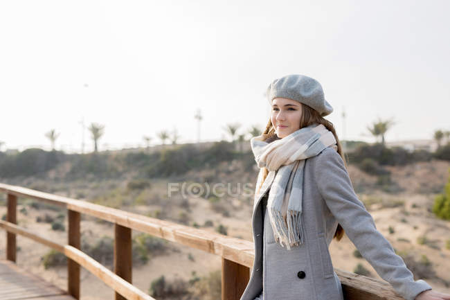 Pretty woman leaning at wooden handrail of boardwalk — Stock Photo