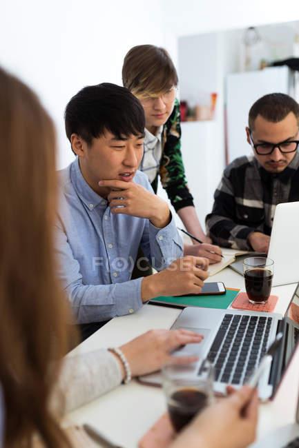 Gruppe von Rassen Zusammensitzen mit Gadgets am Bürotisch — Stockfoto