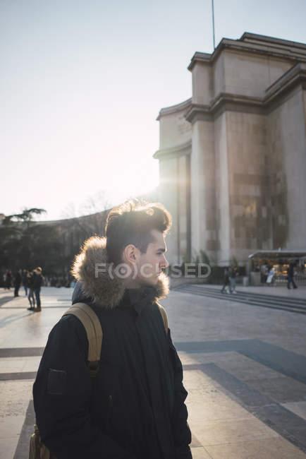 Pensoso giovane turista cammina sulla grande piazza nel chiarore del sole e che osserva via — Foto stock