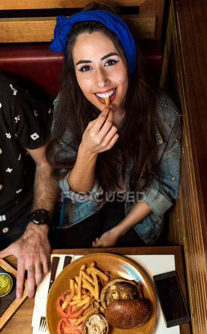 Cheerful young woman eating french fry and looking up at camera — Stock Photo