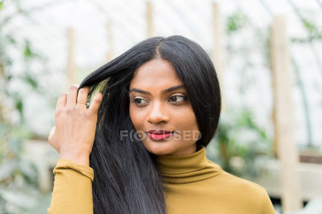 Young Indian woman touching hair and looking away — Stock Photo