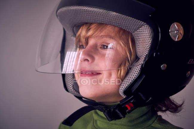 Mignon garçon souriant en casque de moto — Photo de stock