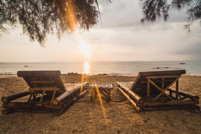 Дві порожні шезлонги на піщаному пляжі на заході сонця — стокове фото