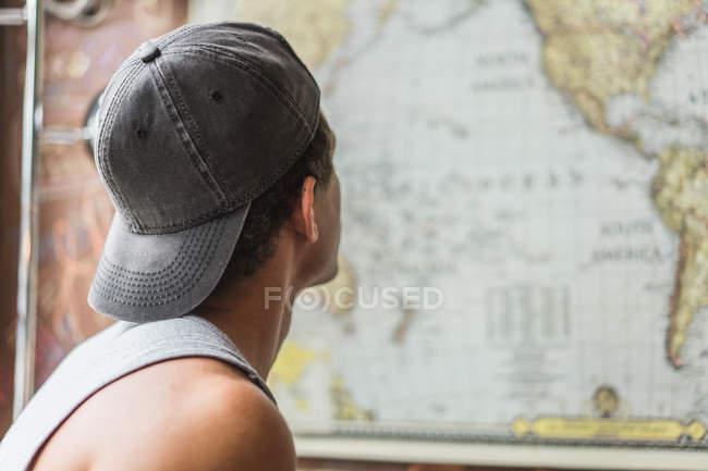 Rückansicht des Jünglings in GAP und Blick auf die Weltkarte auf Wand. — Stockfoto