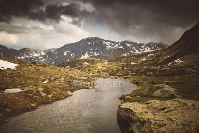 Vista sul piccolo fiume che scorre nella valle della montagna in una giornata nuvolosa . — Foto stock