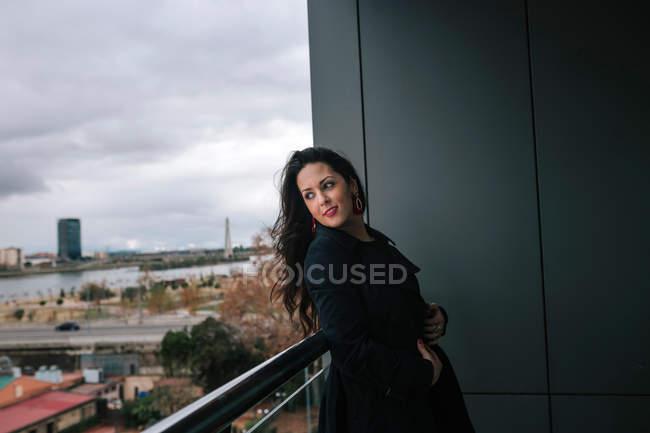 Femme brune joyeuse penché à la balustrade et la recherche. — Photo de stock