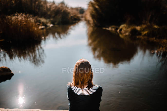 Rear view of woman sitting at water. — Stock Photo
