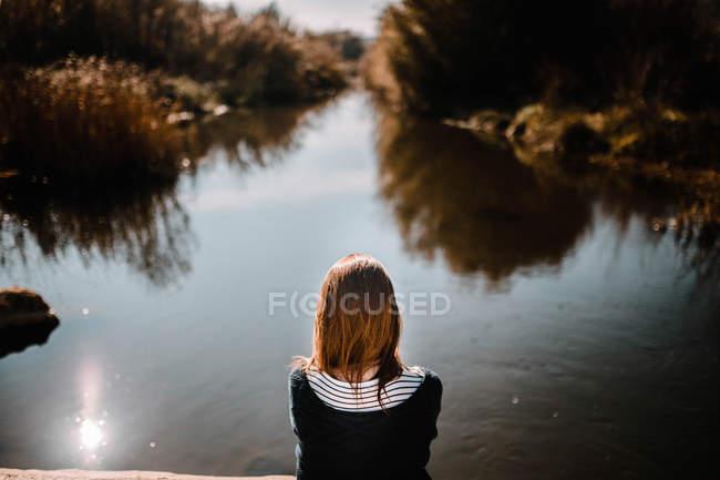 Вид сзади на женщину, сидящую у воды . — стоковое фото