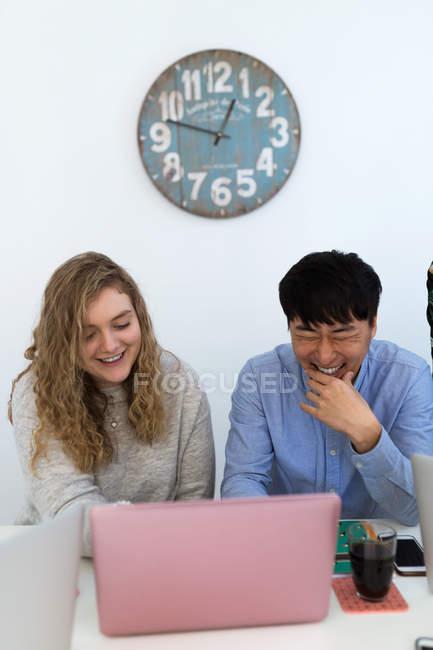 Fröhliche multirassische Kollegen sitzen und lachen über Laptop im Büro — Stockfoto