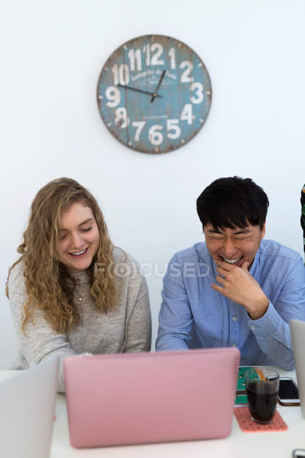Веселых многорасовым coworkers сидели и смеялись ноутбук в офисе. — стоковое фото