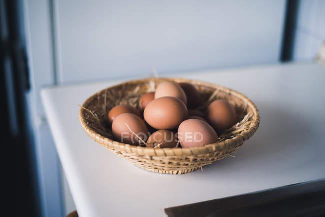 Tigela de palha com ovos de galinha marrom na mesa branca . — Fotografia de Stock