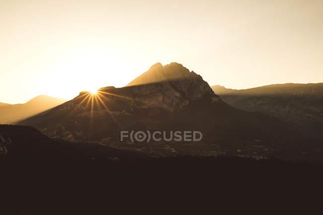 Montagnes en rétro-éclairé pendant le coucher du soleil dans le ciel clair. — Photo de stock