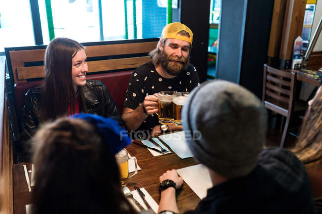 Cheerful happy people clinking glasses of beer at restaurant. — Stock Photo
