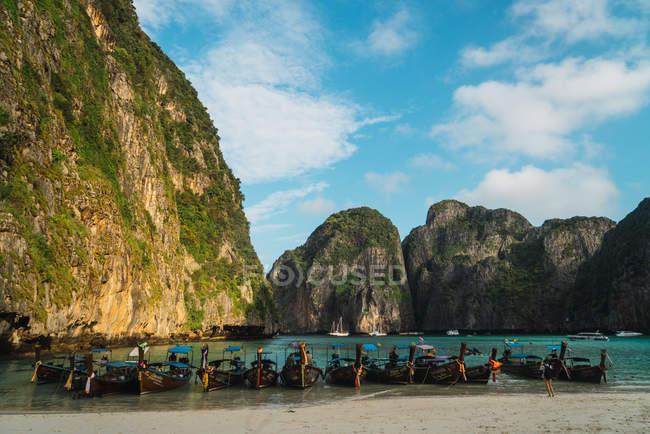 Рядок човни пришвартовані на білопіщаному пляжі тропічною лагуною — стокове фото