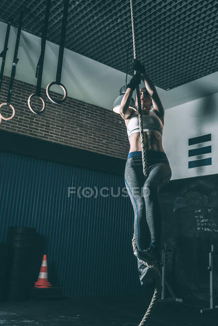 Fit blonde woman climbing rope during training in gym — Stock Photo