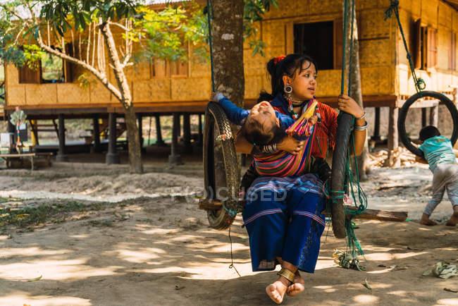 ЧАЙАНГ-РАЙ, Таиланд - 12 февраля 2018 года: Этническая женщина сидит на качелях с ребенком — стоковое фото