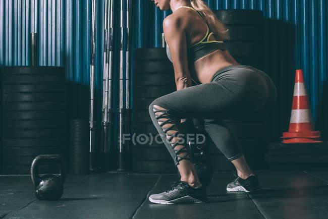 Culture fit femme accroupie dos kettlebell en gym — Photo de stock