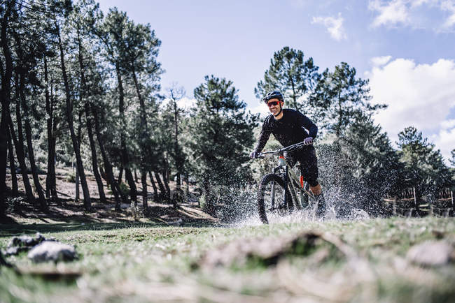 Cheerful cyclist ridding mountain bike and splashes water — Stock Photo