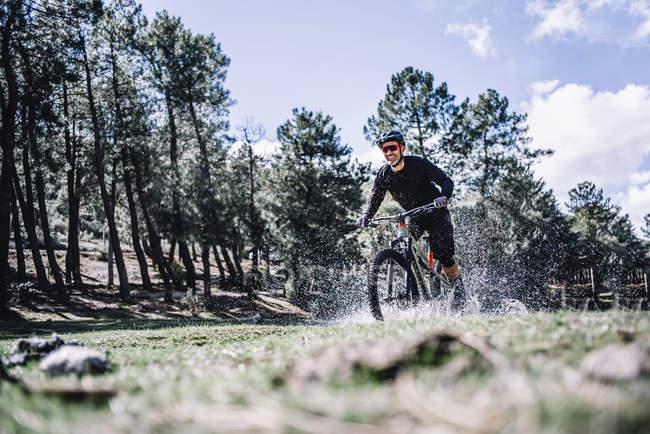 Bicicleta de montanha alegre ciclista cavalgada e salpicos de água — Fotografia de Stock