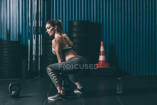 Fit woman doing buttocks workout with kettlebell in gym — Stock Photo