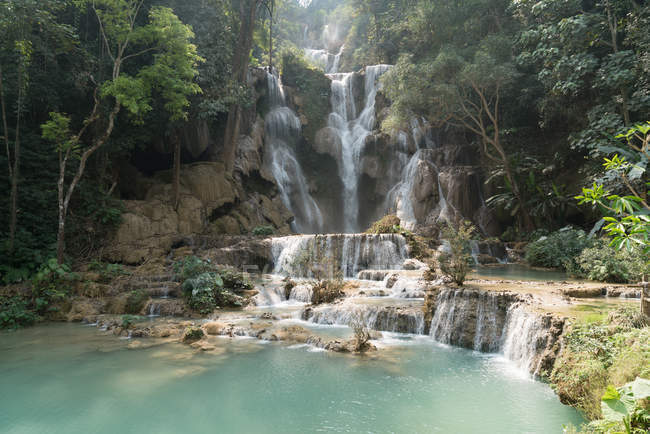 View to tropical waterfall flowing in lake — Stock Photo