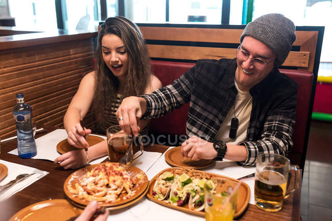 Joyeux jeunes amis assis et manger de la restauration rapide dans le café ensemble . — Photo de stock