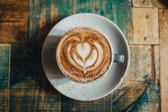 Directamente encima de la vista de la taza de café con leche con flor - foto de stock