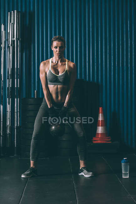 Fit woman working out with kettlebell in gym — Stock Photo