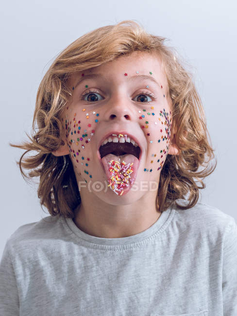 Cheerful boy with confetti on face showing tongue — Stock Photo