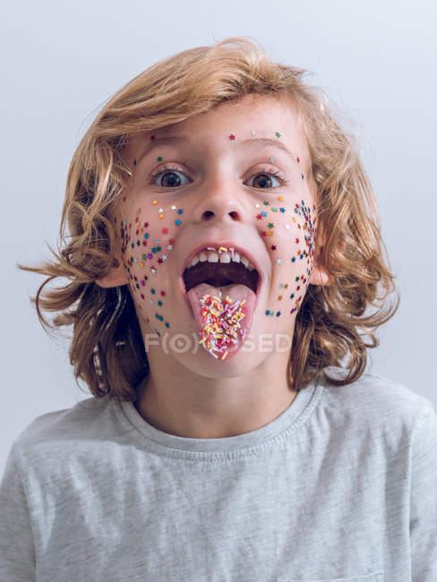 Chico alegre con confeti en la cara mostrando la lengua - foto de stock