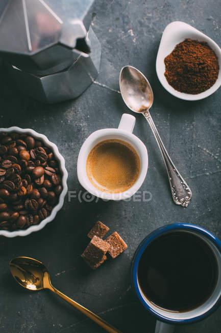 Прямо над видом на чашку кофе и кофейных зерен с молотым кофе — стоковое фото