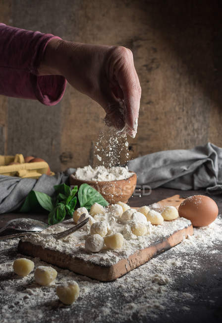 Cultivo mano verter harina en ñoquis crudos en tablero de madera en la mesa - foto de stock