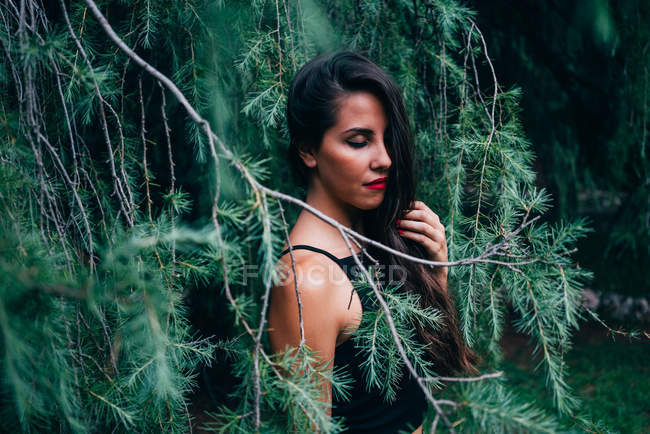 Pretty woman with closed eyes posing in fir branches — Stock Photo