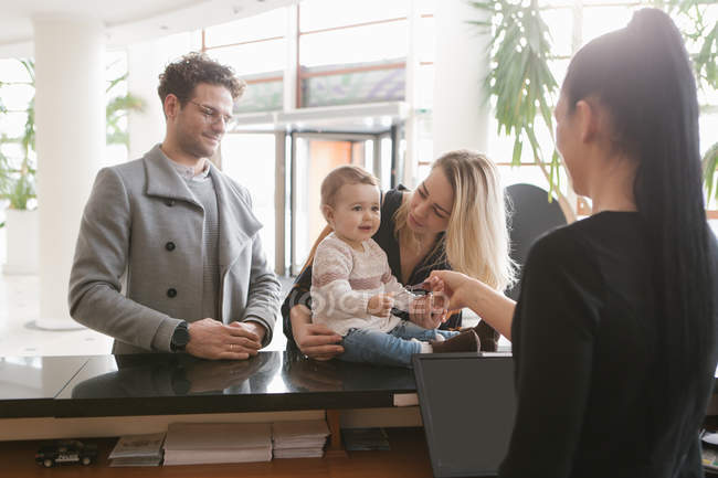Staff worker at hotel reception giving key to family — Stock Photo