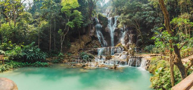 Панорамный вид тропических водопадами впадающих в бирюзовое озеро — стоковое фото