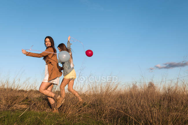 Young women holding hands and running with balloons through sunlit field — Stock Photo
