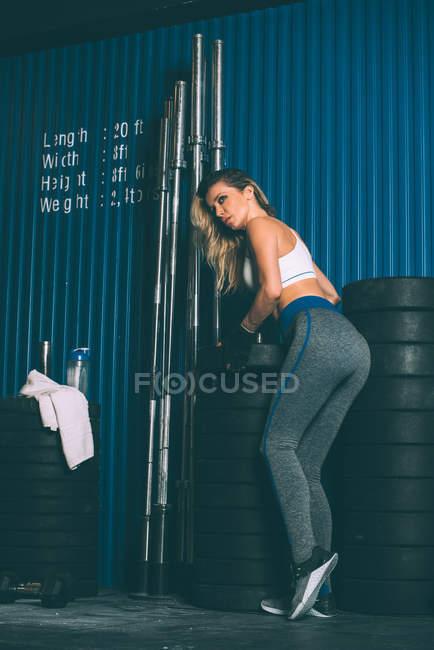 Adapter le poids de réglage de femme blonde tout en travaillant dans la salle de gym — Photo de stock