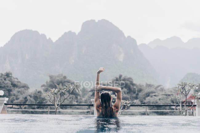 Задній вид жінка у басейні outstretching руку на фоні тропічних гір у дощовий день — стокове фото