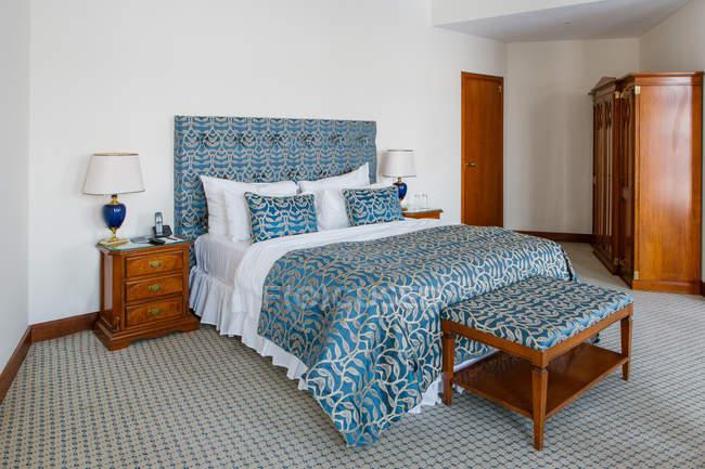 Intérieur de la chambre avec lit bleu et blanc dans la chambre — Photo de stock