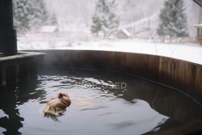 Mulher loira deitada na banheira exterior de mergulho e relaxante — Fotografia de Stock