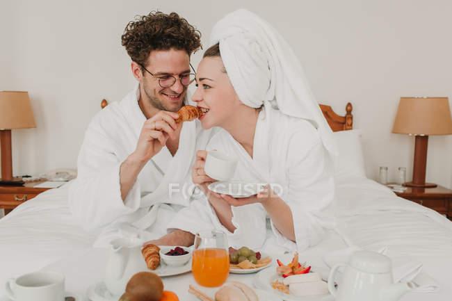 Pareja alegre desayunando en la cama del hotel - foto de stock