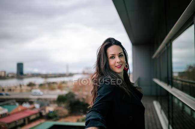 Femme joyeuse penché à la balustrade et souriant à la caméra — Photo de stock