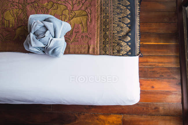 Crop bed with rose-shaped towel — Stock Photo