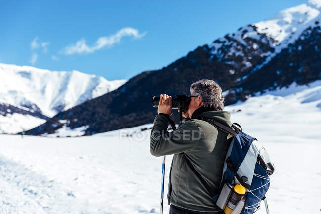 Side view of senior photographer taking pictures in snowy meadow — Stock Photo