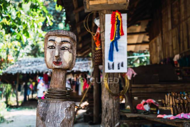 Lustiges Gesicht aus Baum auf Straße eines asiatischen Dorfes geschnitzt. — Stockfoto