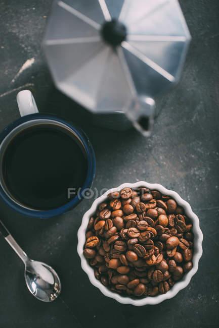 Кофейная чашка с кофейными зёрнами и пустая чашка — стоковое фото