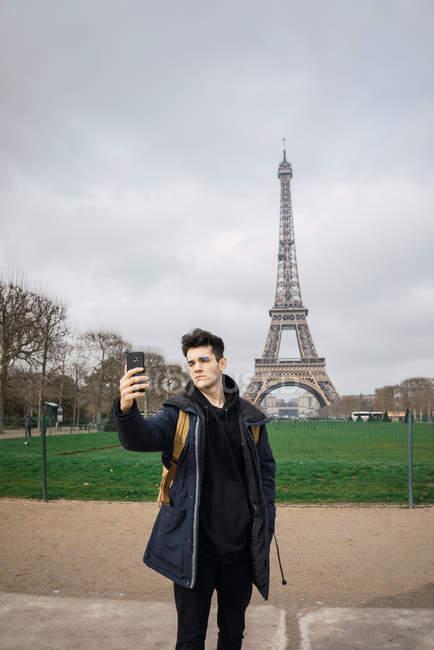Uomo giovane turista che sta con telefono e presa selfie su sfondo della Torre Eiffel — Foto stock