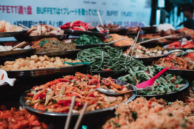 Assortment of traditional Asian food on counter at market. — Stock Photo