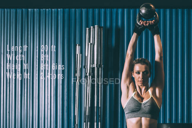 Fit woman training lifting kettlebell in gym — Stock Photo